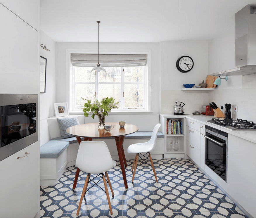 White dining nook situated in the kitchen's corner and accented with a patterned tile flooring. It has built-in seating fitted with dusty blue cushions along with a round dining table and modern white chairs.