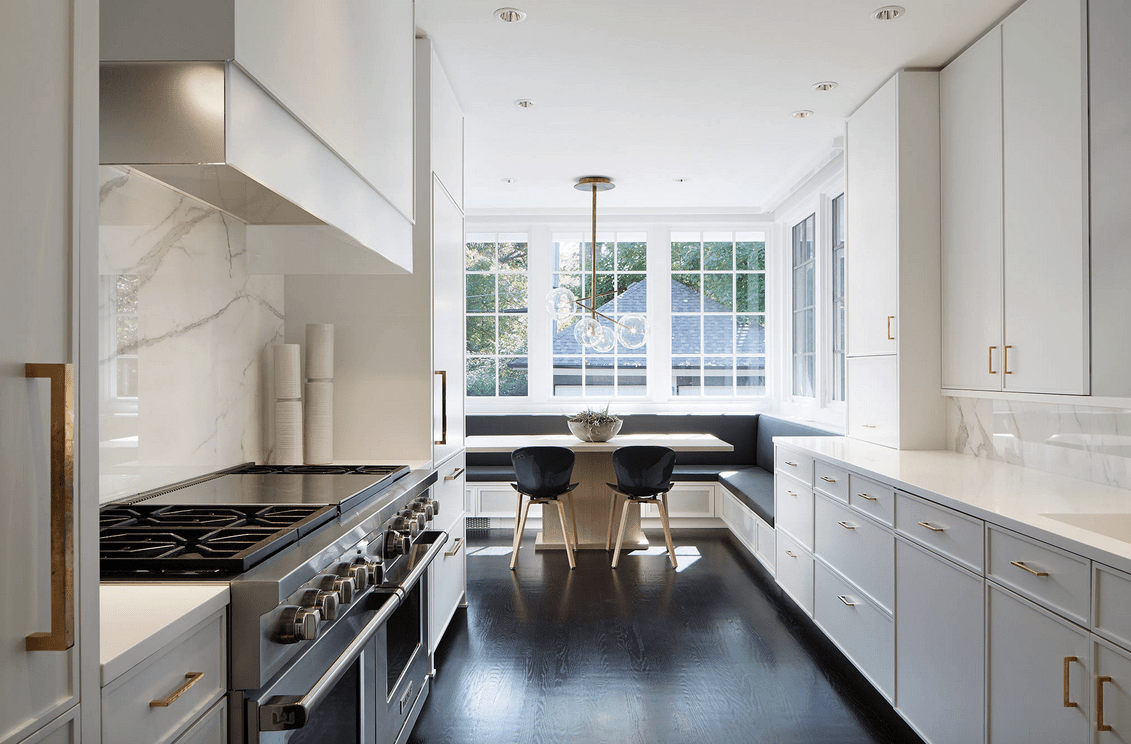 Deluxe kitchen boasts white cabinetry fitted with brass pulls and a dining nook by the glass windows with built-in seating illuminated by a contemporary chandelier.