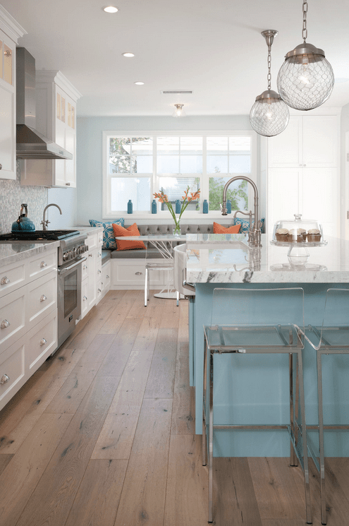 Beach style kitchen with a dining nook in the corner offering a white dining table and gray tufted built-in bench accented with coral and blue pillows.