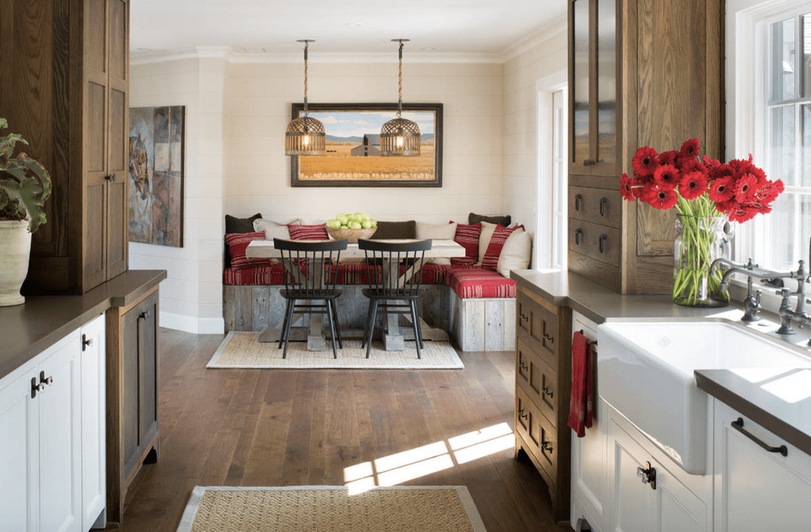 This dining nook features a rustic dining table with black chairs and wood plank built-in seating topped with red cushions and fluffy pillows.