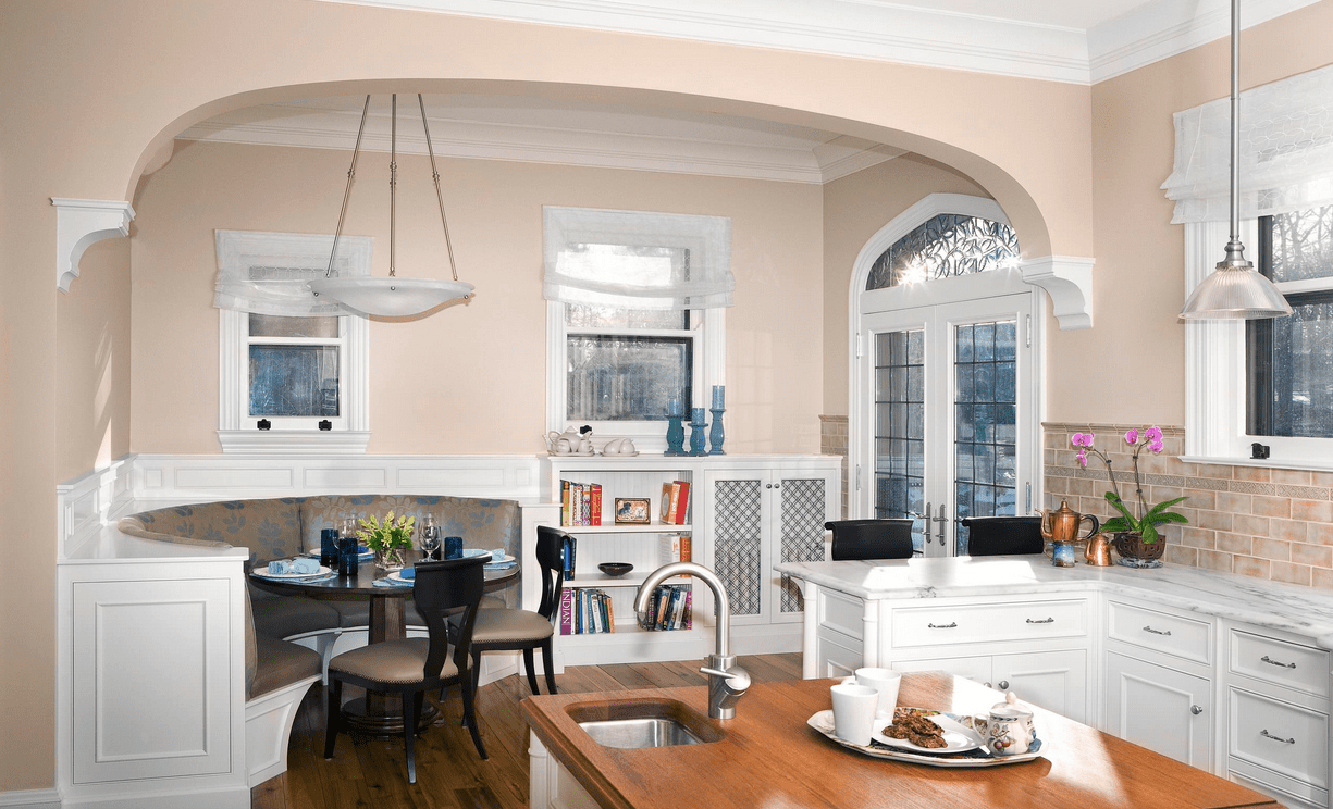 Charming kitchen with a dining nook in the corner that sits beside the open shelving. It has a built-in curved seat and a round dining table with beige cushioned chairs.