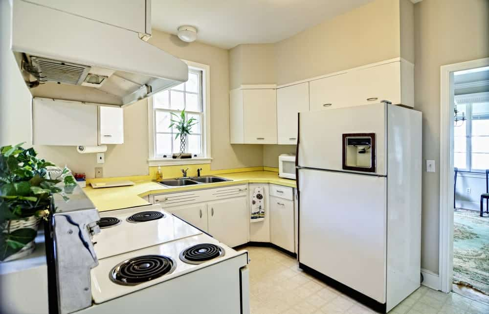 U-shaped kitchen with white cabinetry and appliances accented with a yellow countertop that's fitted with stainless steel dual sink.