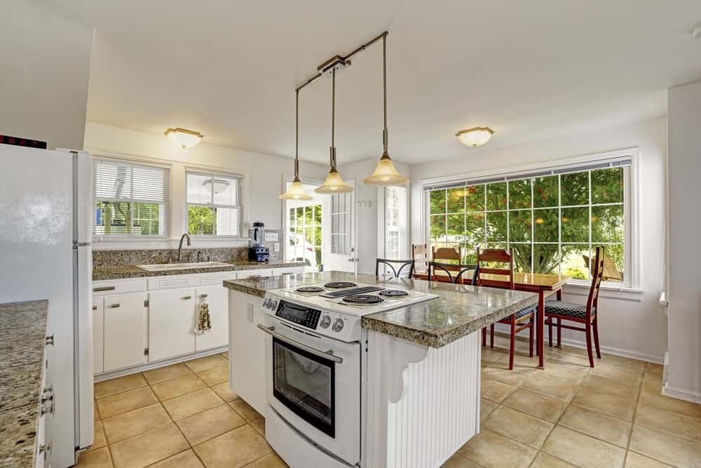 Airy dine-in kitchen features white cabinetry and a kitchen island that's topped with a marble counter and fitted with a white range illuminated by pendant lights.