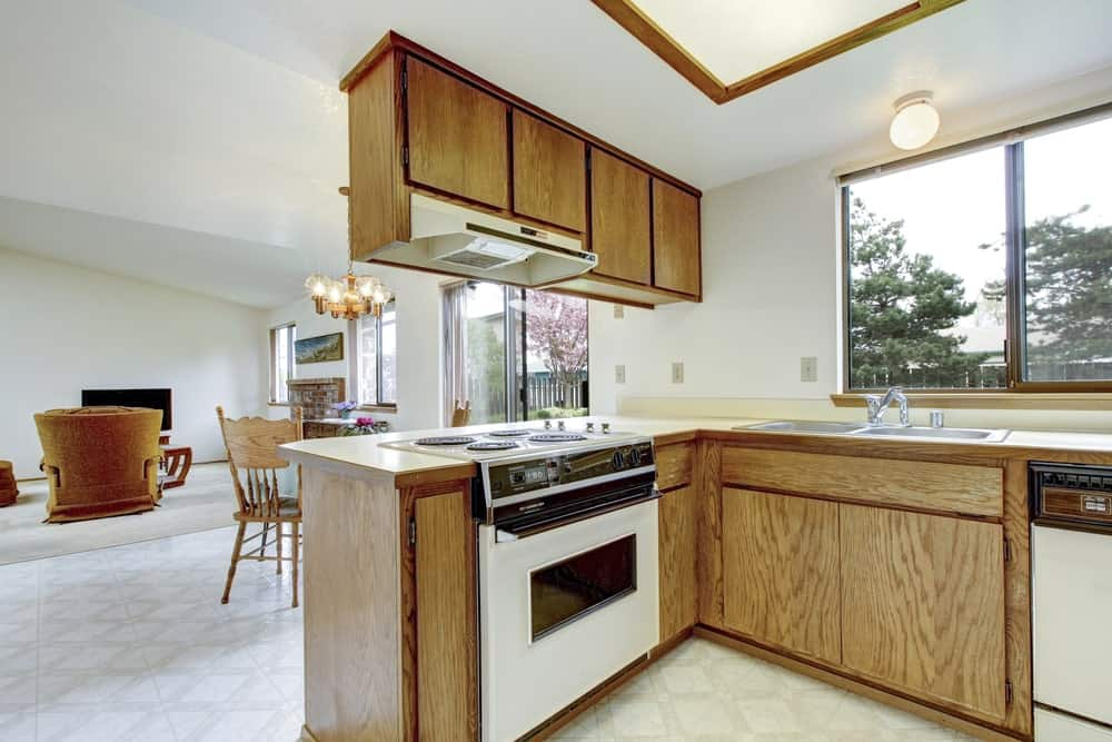 An L-shaped kitchen showcases white appliances that blend perfectly with the natural wood cabinetry.