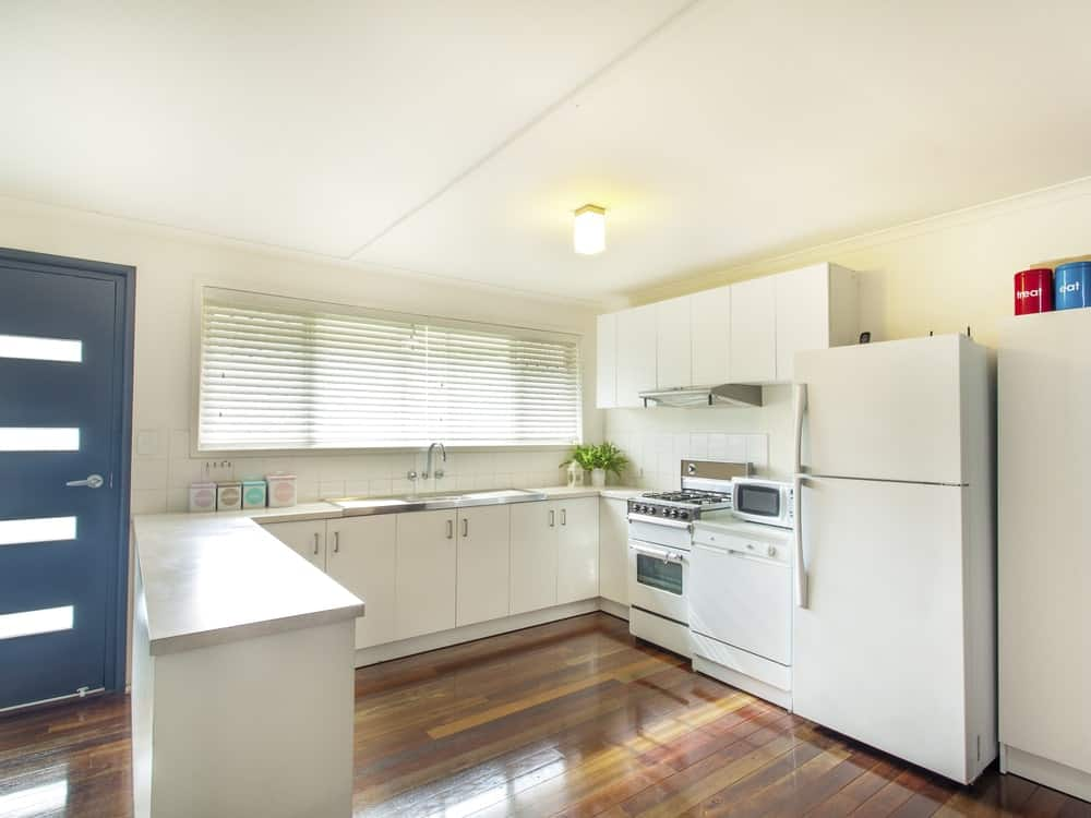 Fresh kitchen with rich wood plank flooring and glass windows covered with blinds. It has sleek cabinetry and stainless steel vent hood suspended over the white range.