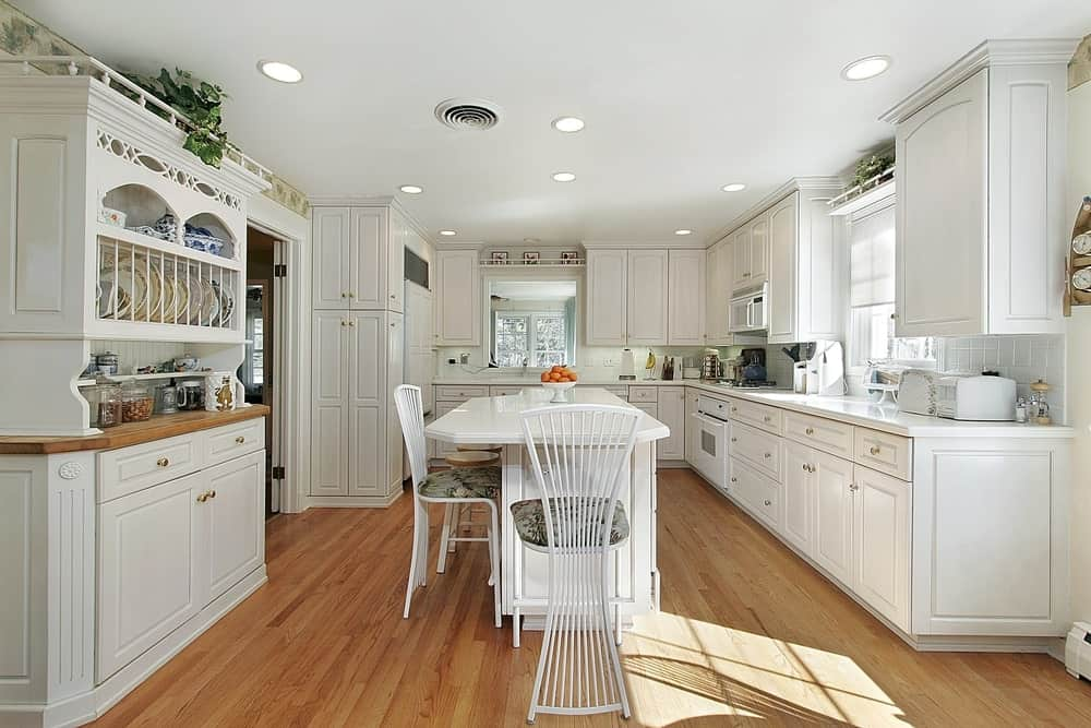 Classic white kitchen boasts a breakfast island that's paired with stylish counter chairs and surrounded with white cabinetry and appliances.