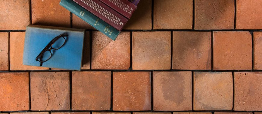 A reclaimed terracotta tiles flooring topped by a few books.