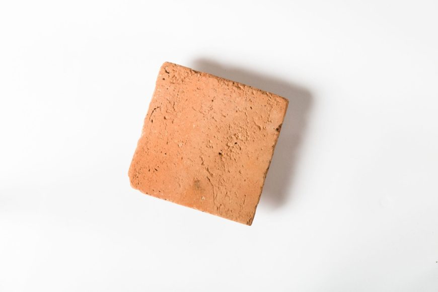 A focused shot at this single terracotta tile on a white background.