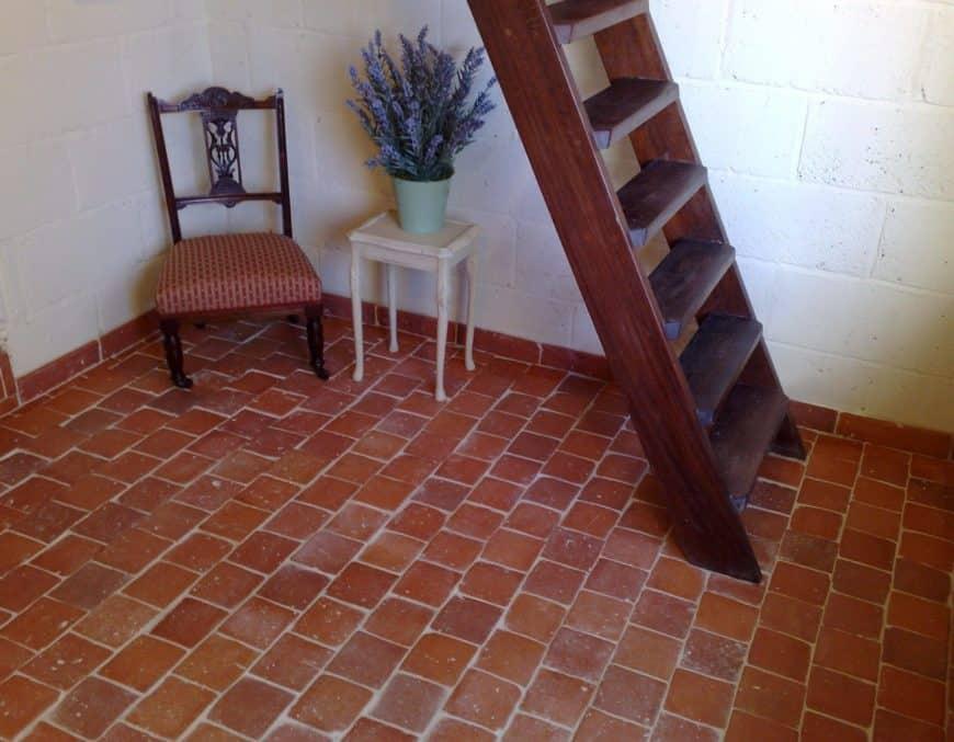 Terracotta brick tiles flooring in the home's landing area.