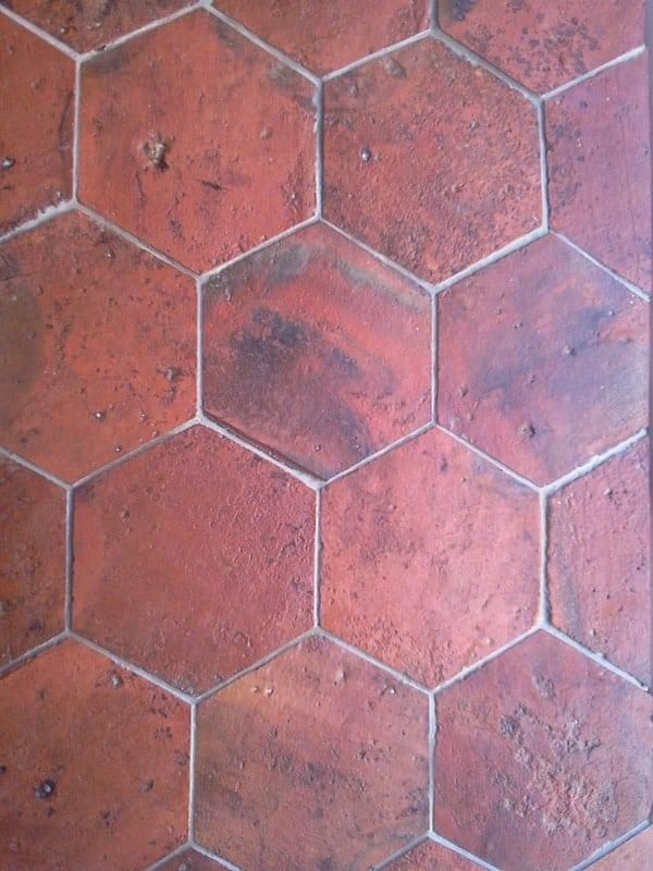 A reddish hexagonal reclaimed terracotta tiles flooring.