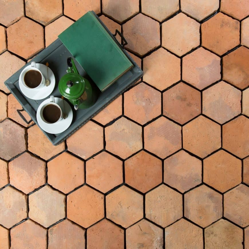 A clean and nice hexagonal terracotta tiles flooring with a tray on top with a coffee set and a book on it.