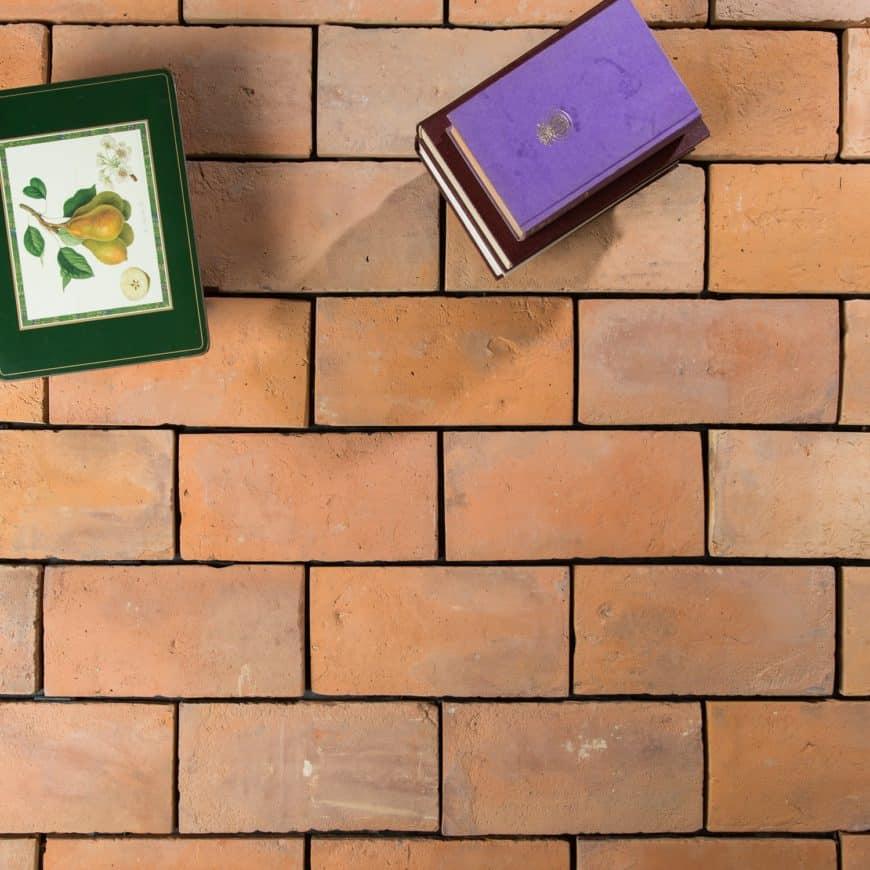 Books on top of the brick terracotta tiles flooring.