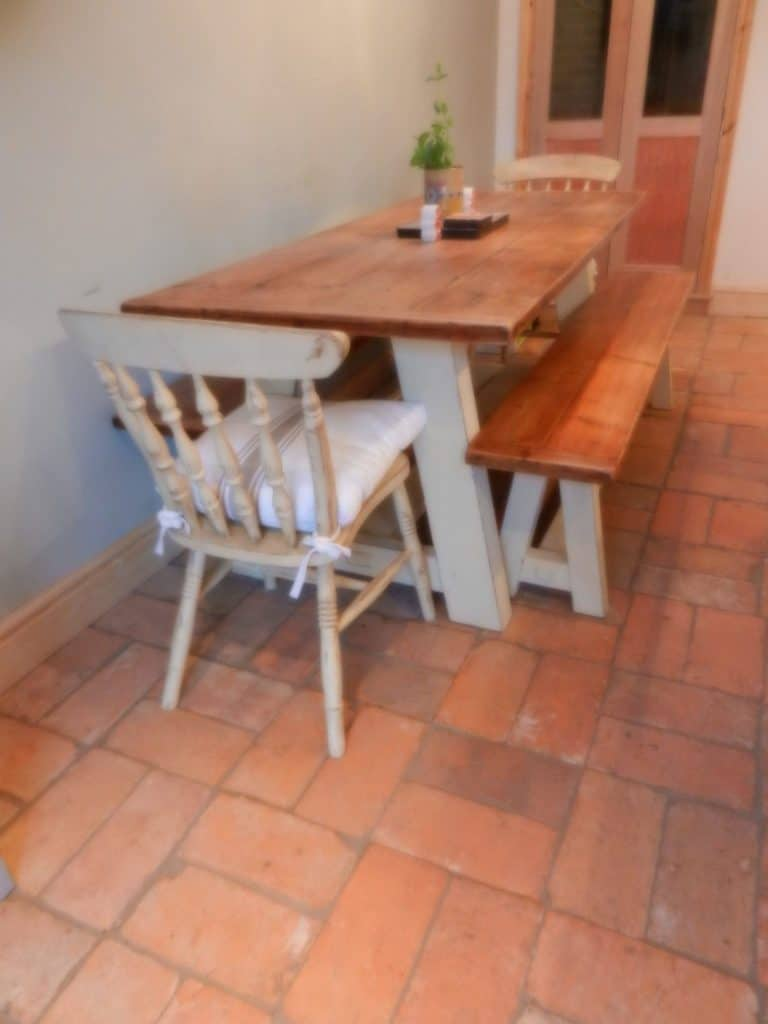 A rectangular dining table set on top of the terracotta brick tiles flooring.