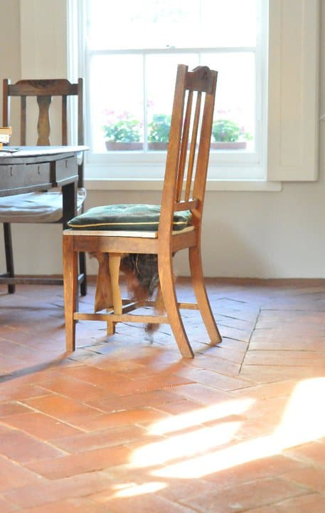 A focused shot at a wooden chair on top of the terracotta brick tiles flooring.