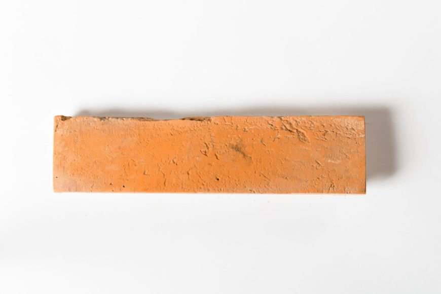 A focused shot of a single brick terracotta tile on a white background.