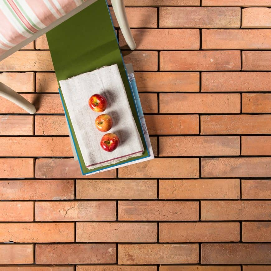 Warm terracotta brick tiles flooring with apples on top near the chair.