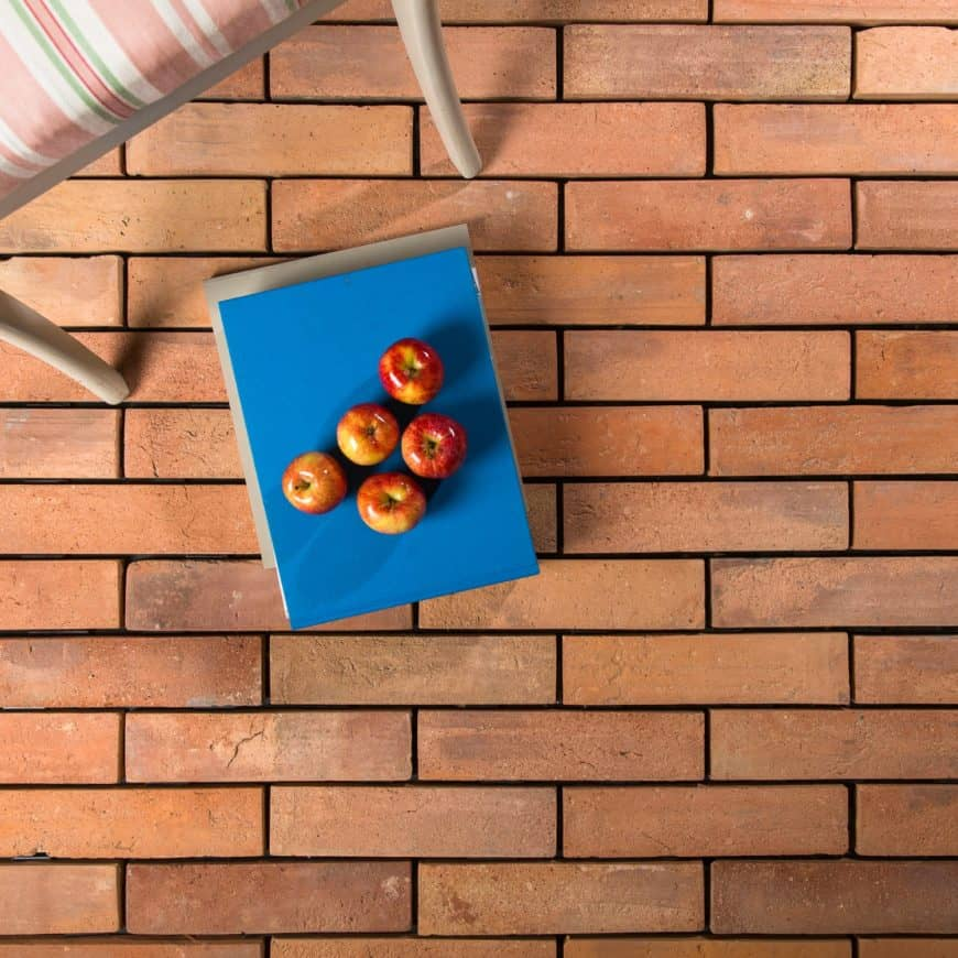 Terracotta brick tiles flooring with apples on top of it.