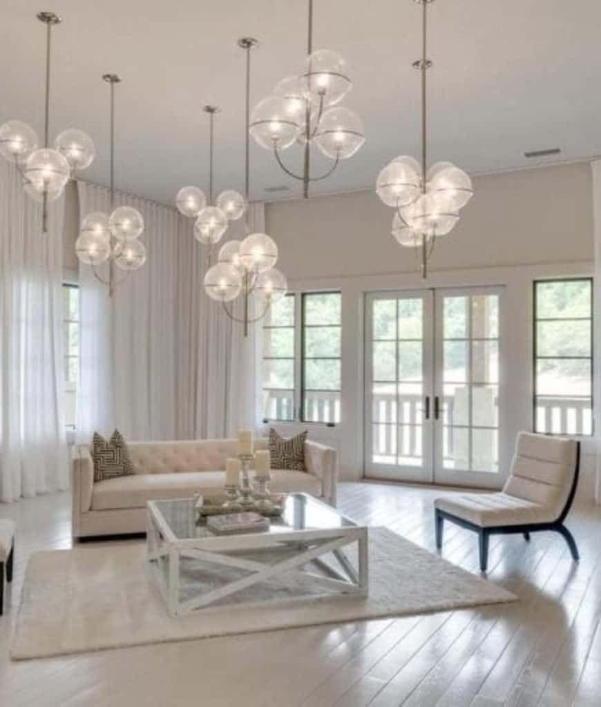 White living room filled with glass globe chandeliers that hung over the tufted sofa, chair and glass top coffee table that sits on a shaggy rug.