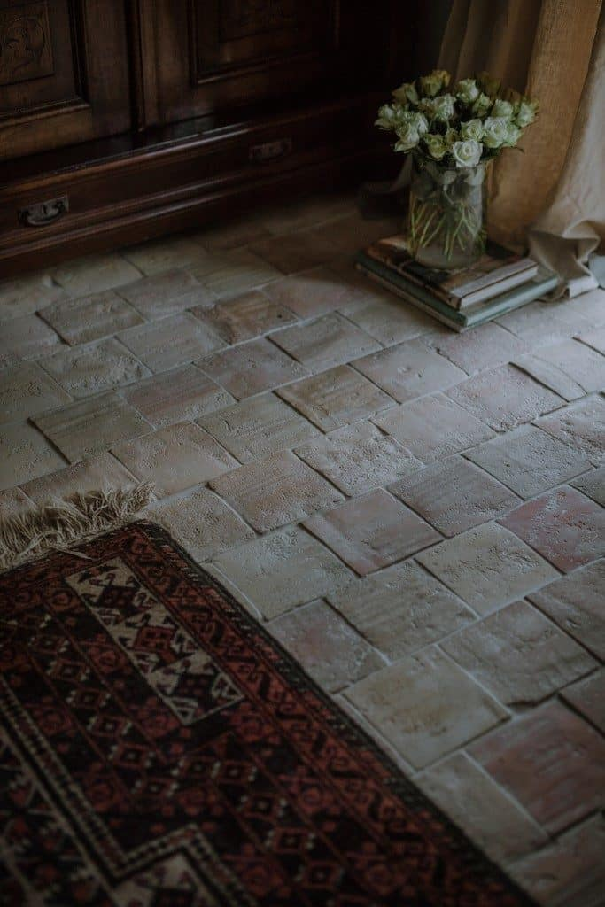 Square terracotta tiles flooring topped by a classy rug.
