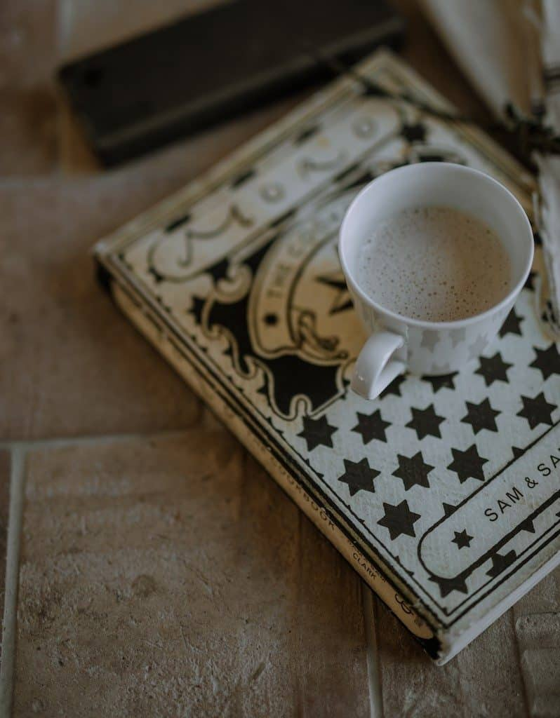 Square terracotta tiles floors with a book on top of it along with a cup of coffee on top of the book.