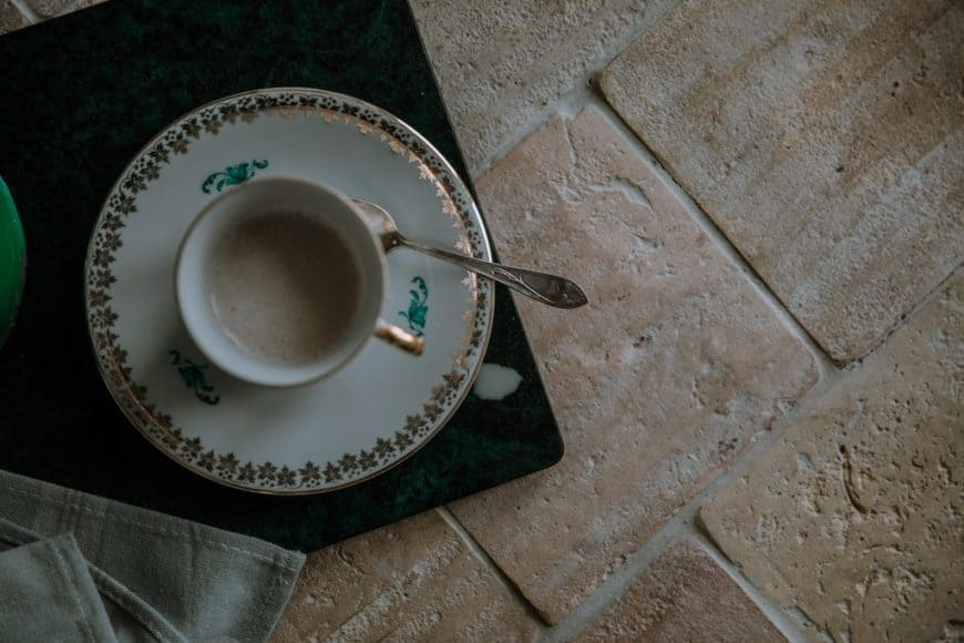 A close up look at this coffee on top of a saucer placed on the light terracotta tiles floors.