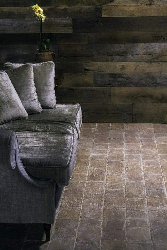 Pale terracotta tiles flooring with a gray couch on it.