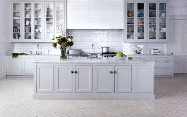White-themed kitchen with stylish light terracotta tiles flooring.