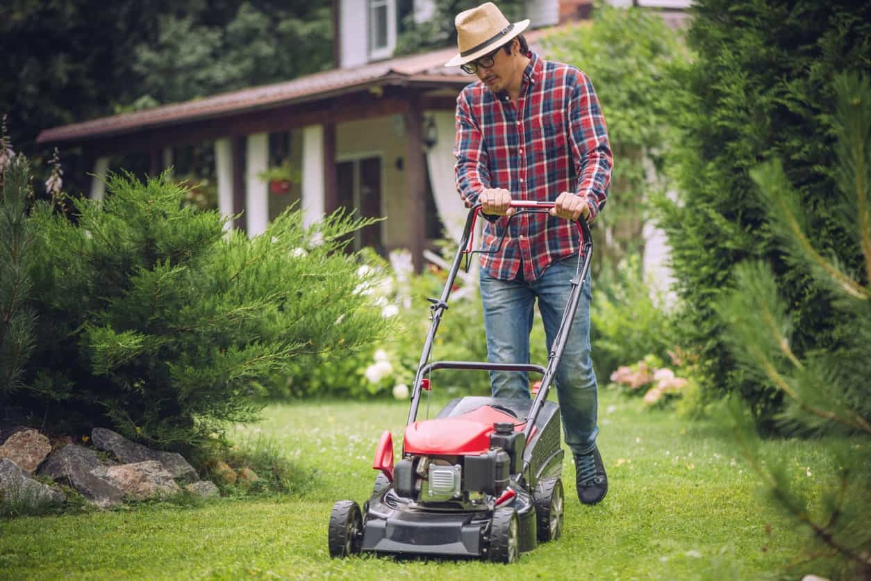 Man mowing the garden lawn with a lawnmower.