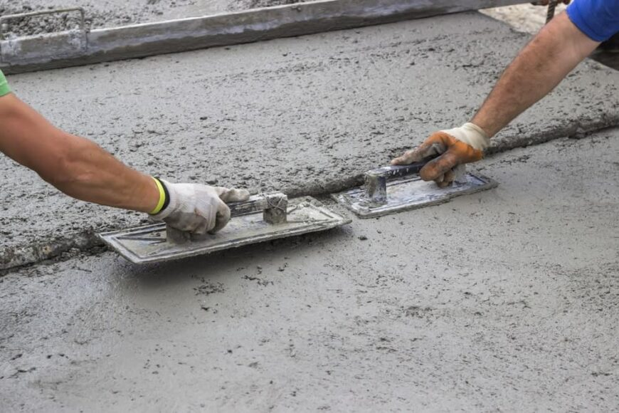Two workers leveling a concrete surface with trowels.