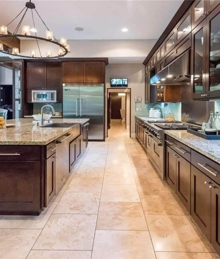 Galley kitchen with glass front cabinets and a wooden breakfast island fitted with a sink and oven. It has a round chandelier and stainless steel appliances inserted on the wooden cabinetry.