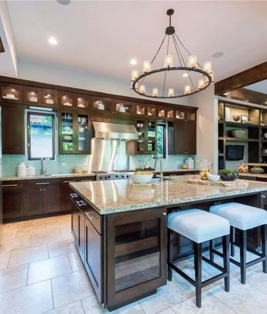 A round chandelier illuminates this kitchen boasting a central island with built-in wine fridge and white bar stools over tiled flooring.