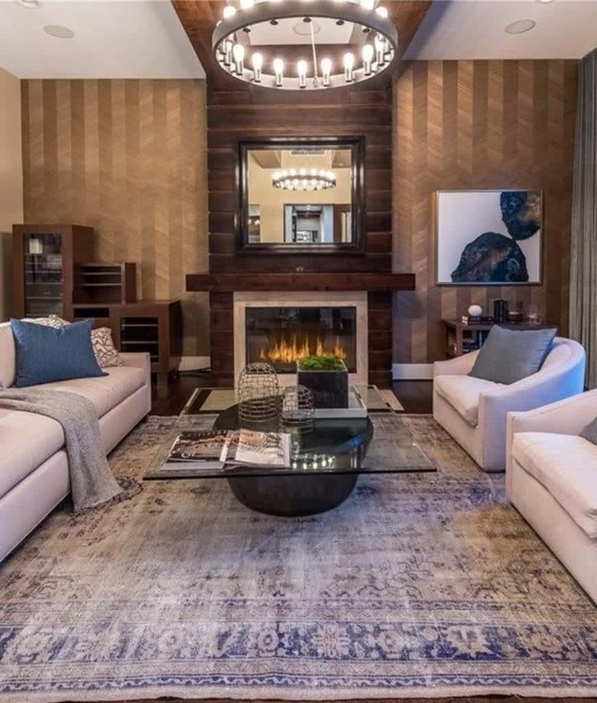 A glass top coffee table sits in between the gray sofa and round back chairs in this living room with round chandelier and modern fireplace.