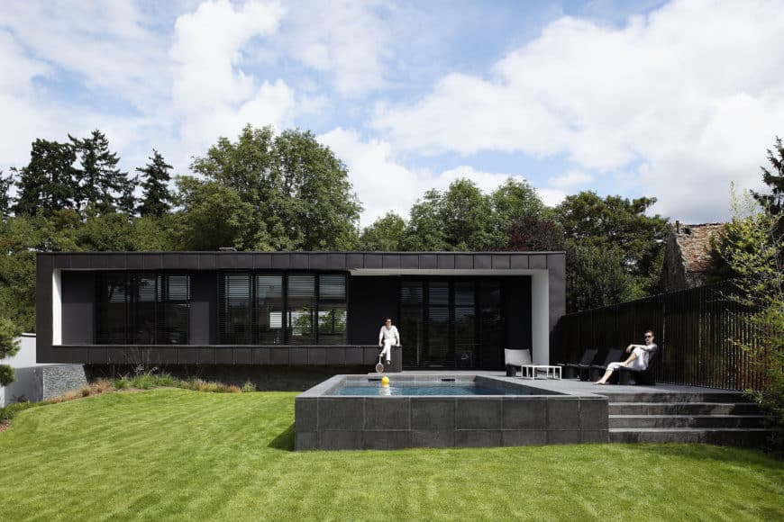 A black modern home featuring a swimming pool, a lounging area and a well-maintained lawn area.