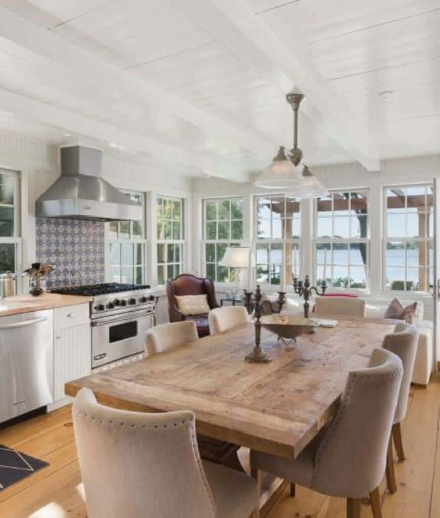 Airy eat-in kitchen features stainless steel appliances and a natural wood plank dining table surrounded with beige upholstered chairs.