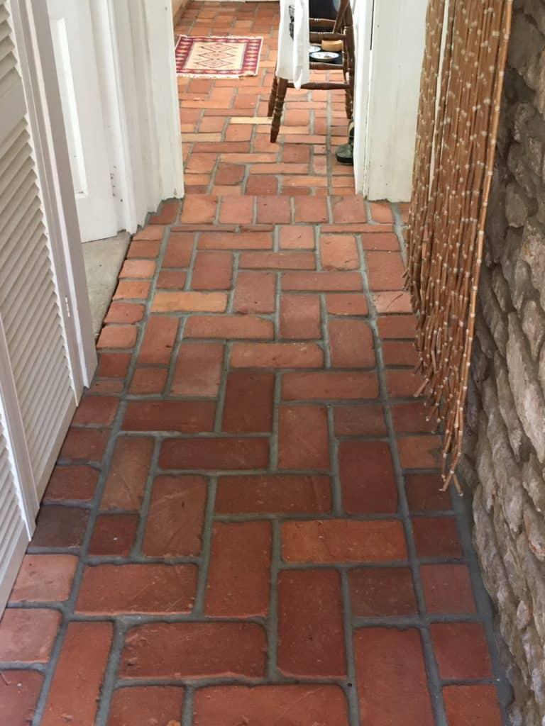 Reddish terracotta tiles flooring in the home's hallway.