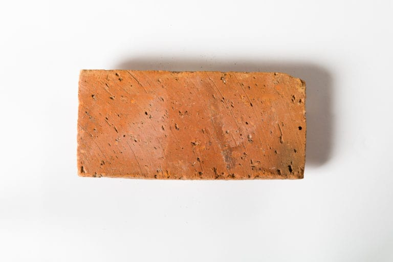 A warm terracotta tile on a white background.