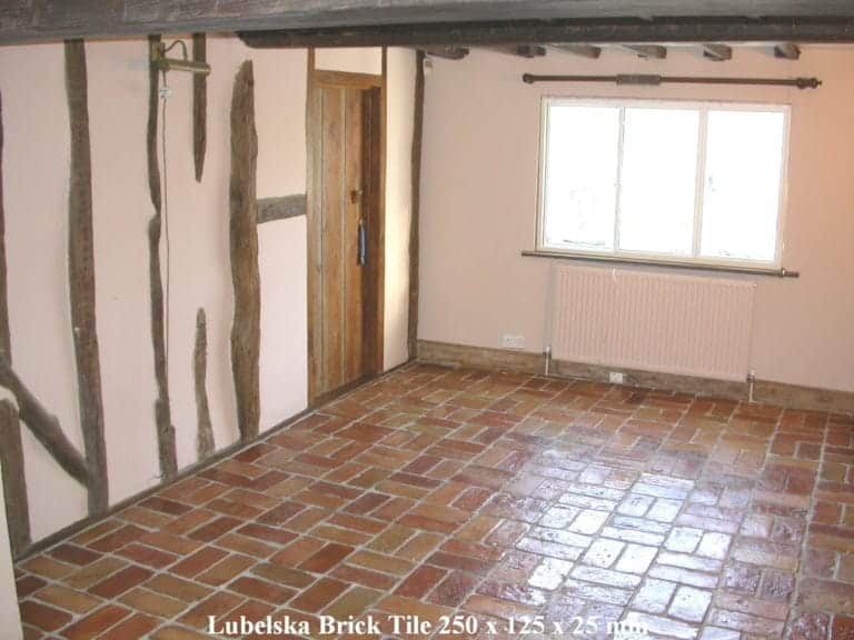 An empty room with warm brick terracotta tiles flooring.