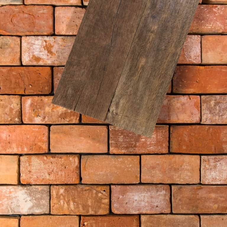 Close up look at this warm terracotta brick tiles flooring with a wood plank on top.