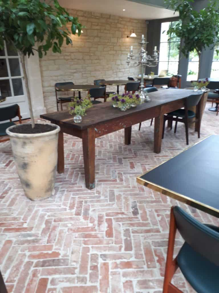 A classy dining area featuring brick terracotta tiles flooring.