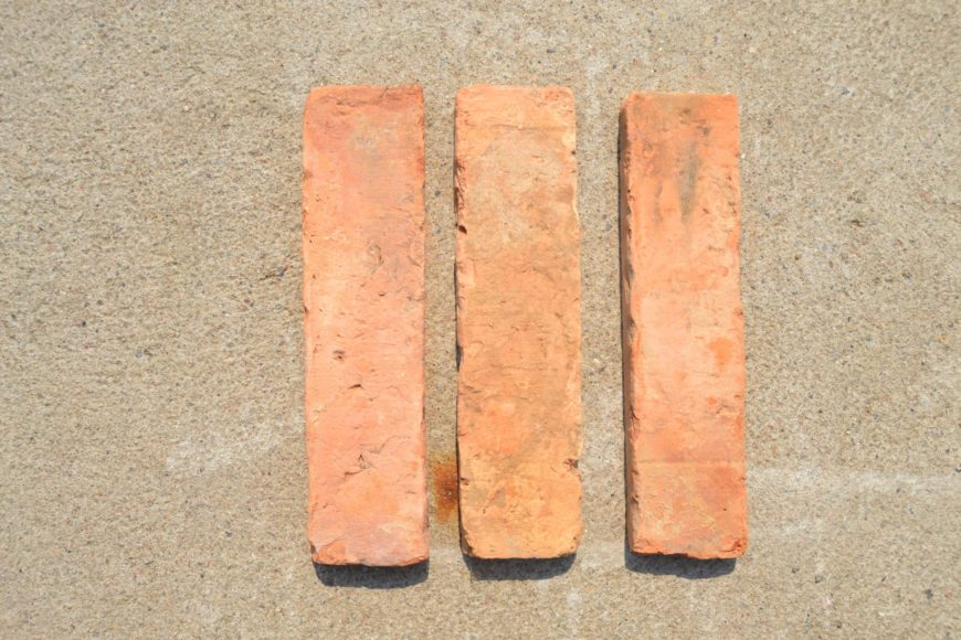 Three pieces of warm terracotta tiles, vertically set.