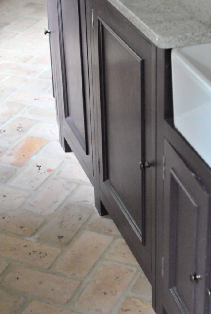 A close up look at this home's kitchen and sink counters along with brick terracotta tiles flooring.