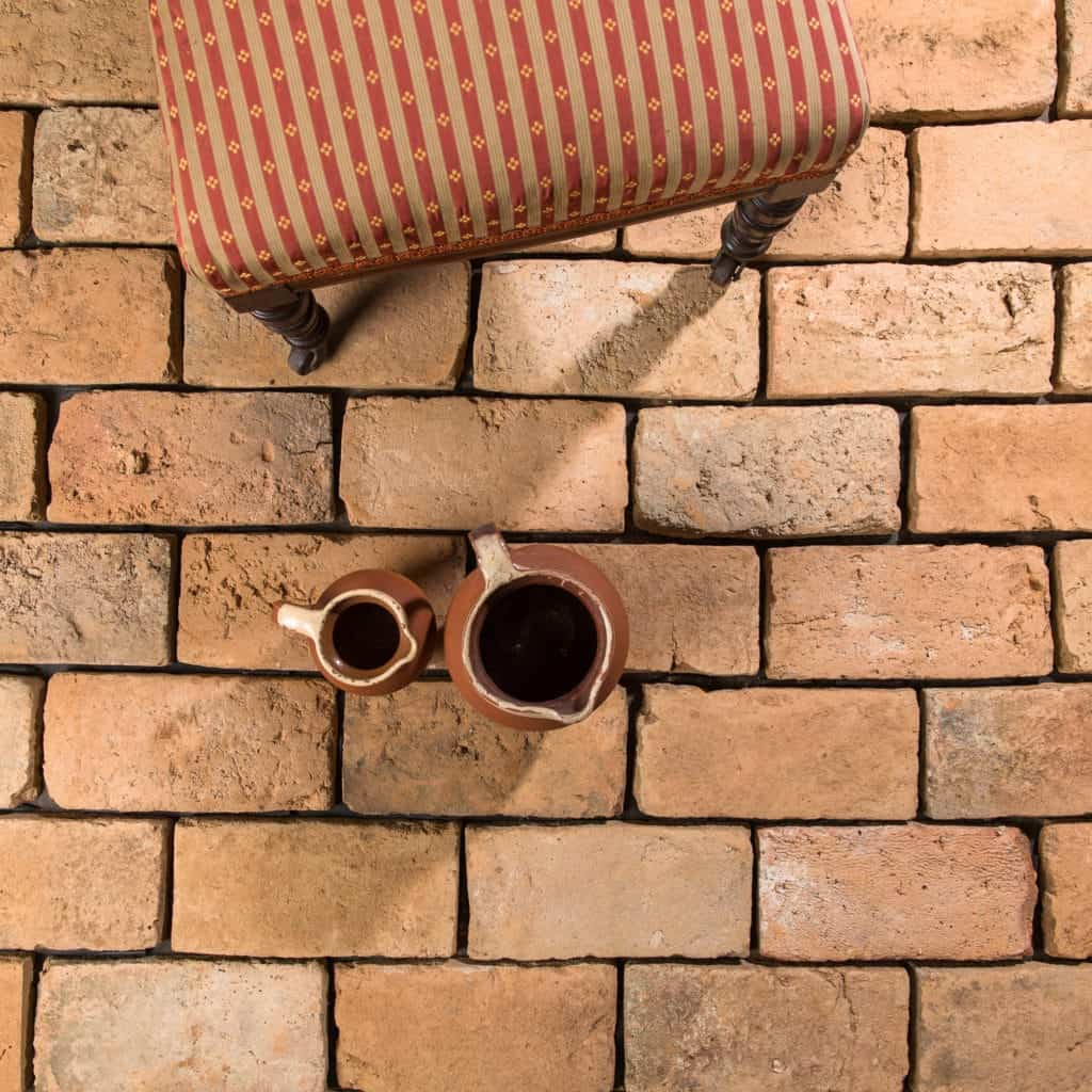 Small and large pitcher on the light terracotta brick tiles flooring.