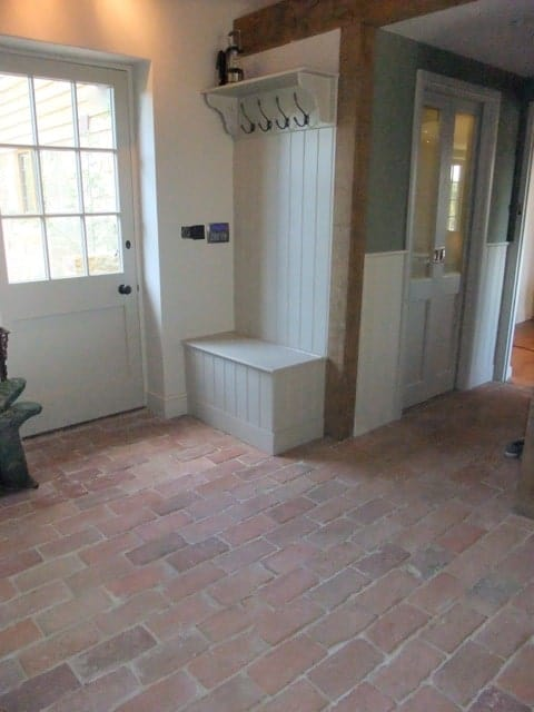 Mudroom entry with brick terracotta tiles flooring.