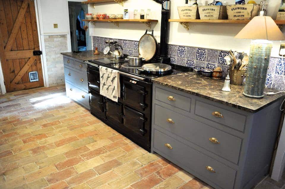 Small kitchen area with stylish kitchen counters and brick terracotta tiles flooring.