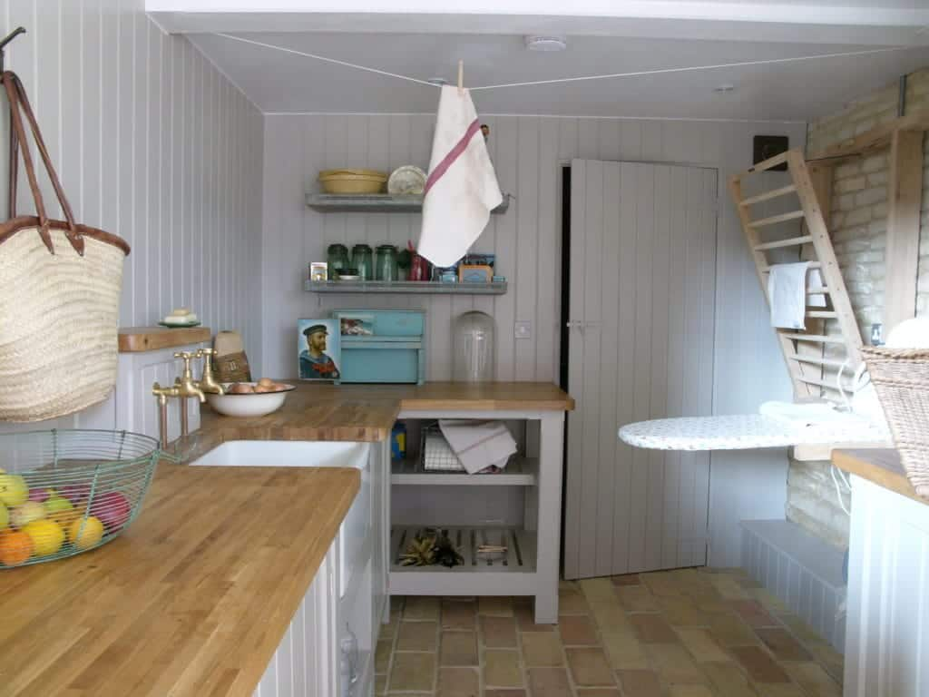 A small laundry and kitchen area with brick terracotta tiles flooring.