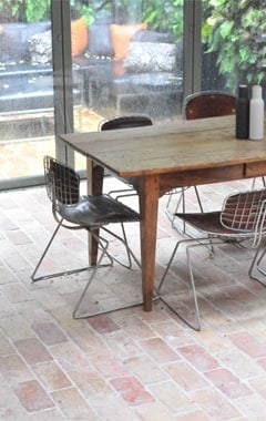 Small dining table set on top of the terracotta brick tiles flooring.