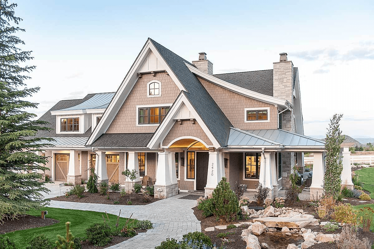 This is a Craftsman-Style house that looks stunning against a sunset with its wilderness landscape that leads to a warm and welcoming entryway and white stone pillars surrounding the house. This is perfectly matched by high angled roofs and stonework chimneys.
