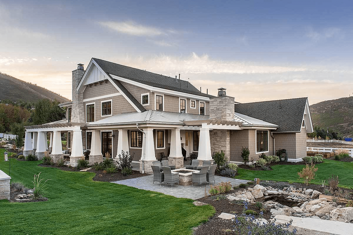 This spectacular house has high arches and gray roofs that match the surrounding mountains. It has a comfortable outdoor hearth that matches the stone chimneys and gray walls that contrast the charming landscape of rocky stream surrounded by grassy lawns.