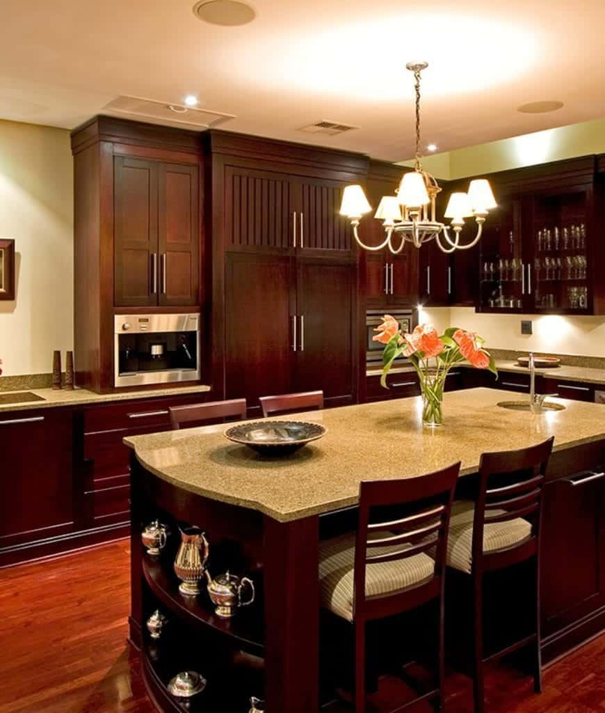 Warm kitchen with dark wood cabinetry and matching breakfast island fitted with a round sink and open shelving.
