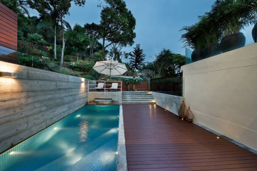 A swimming pool beside the home's deck leading to a perfectly placed lounging area.